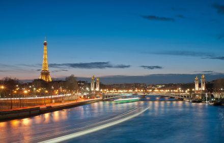 Vista do rio Sena com a Ponte Alexandre III ao fundo e a torre à esquerda.